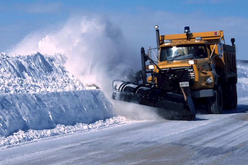 image shows a snow drift with a large yellow bulldozer at the side of it