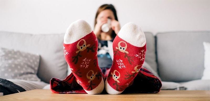 image shows a lady sat on a sofa drinking from a cup with red reindeer socks on