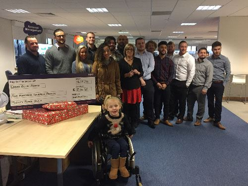 image shows ram tracking team with girl in wheelchair and cheque for charity
