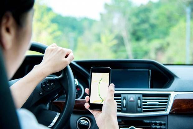 image shows someone driving with a mobile phone in their hand
