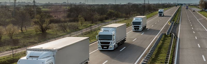 Image shows four large white trucks travelling on a motorway
